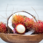 Side View of Split Coconut and Rambutans in a Wood Bowl